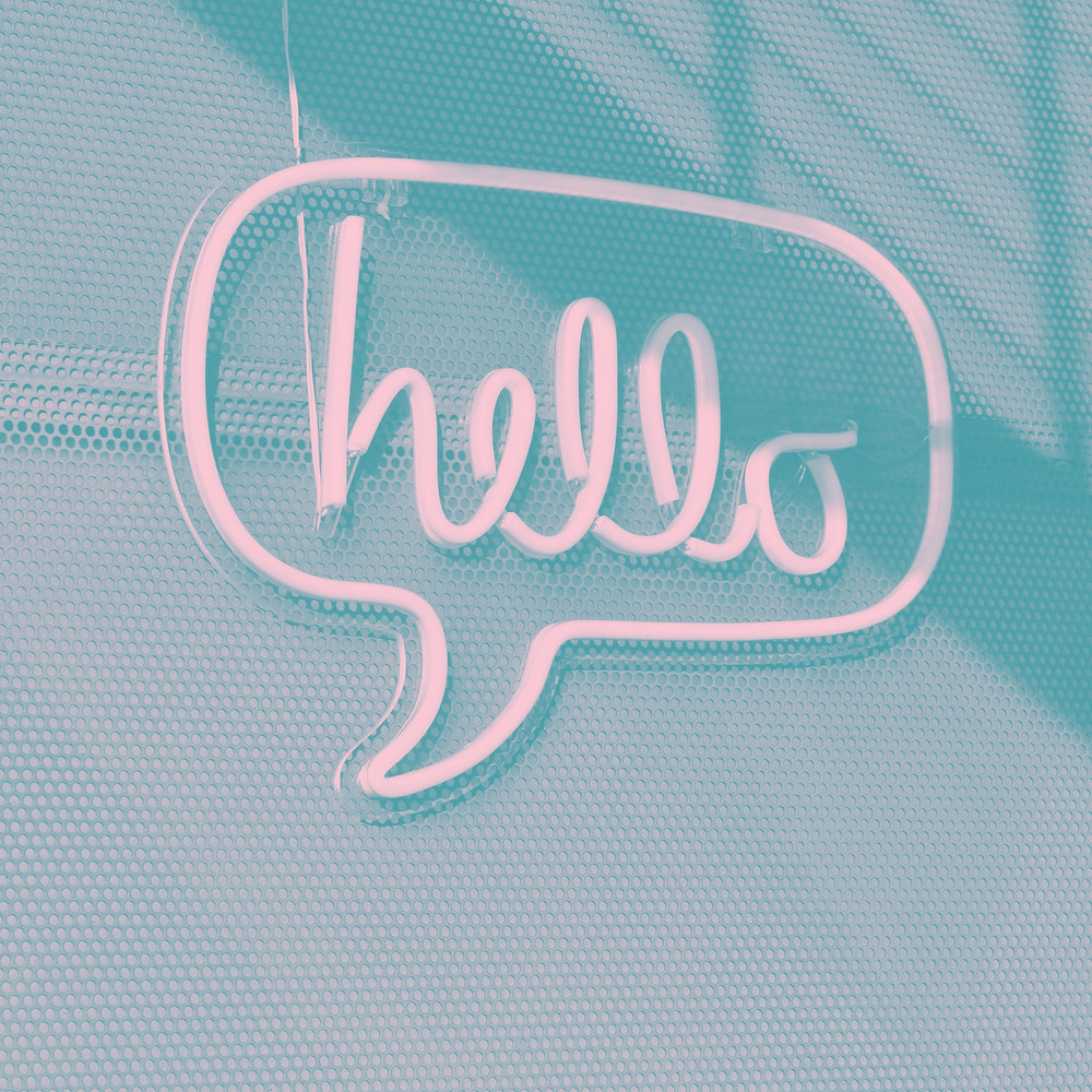 A white neon sign on a light blue background that reads hello in a speech bubble