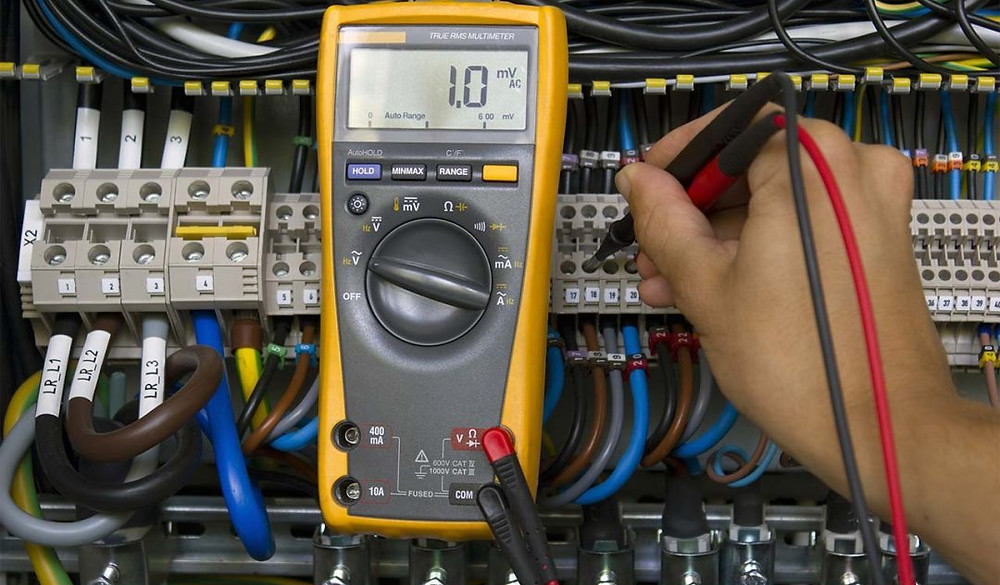 Commercial Electrician testing electrical panel in a commercial building