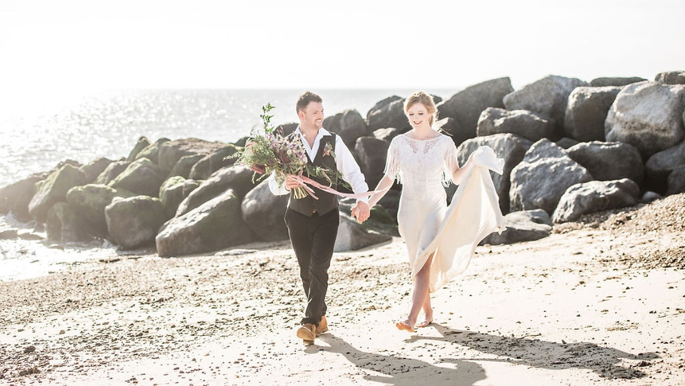 Newly married bride and groom walk barefoot on Essex beach
