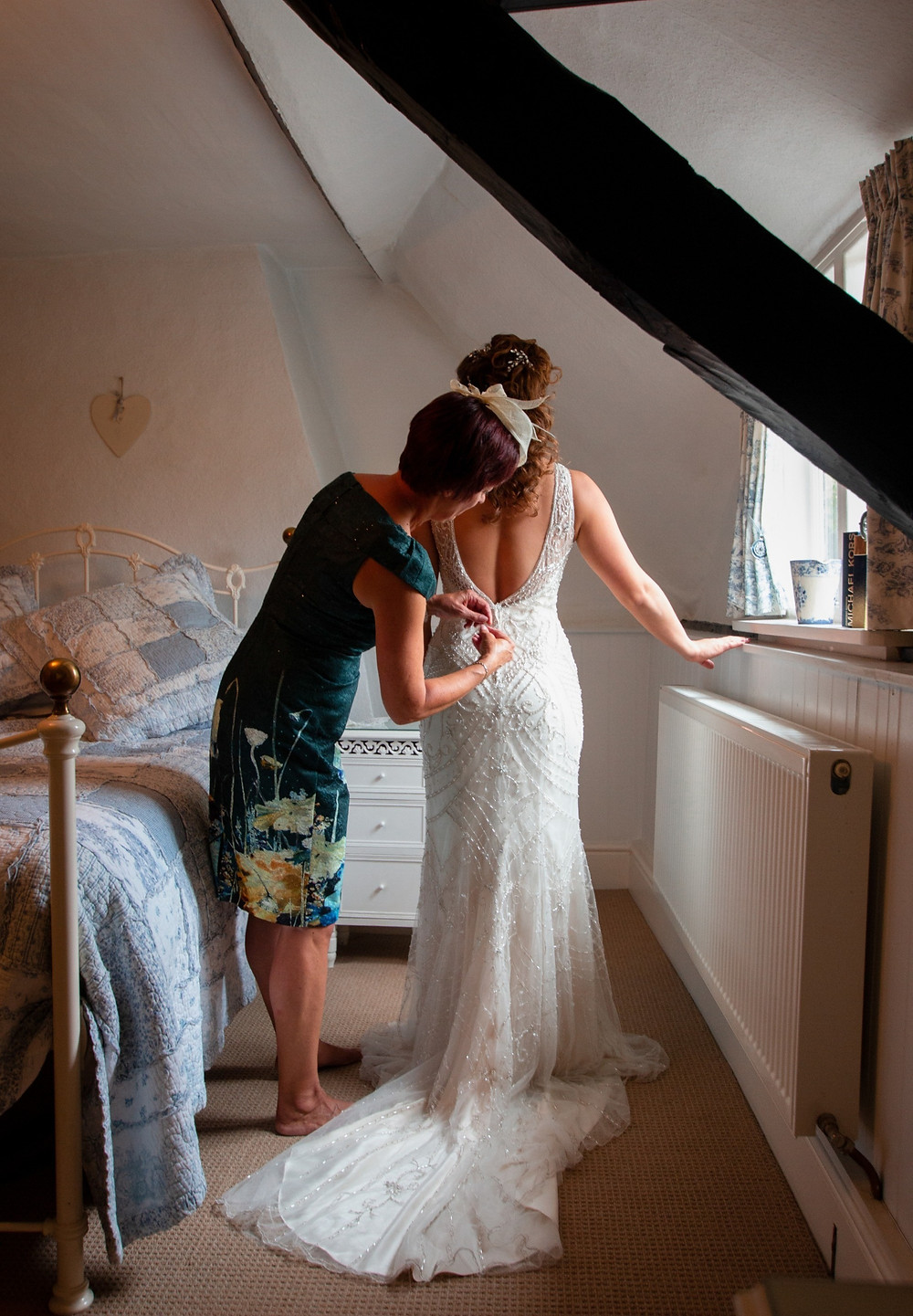 Mother of the bride helping bride into dress