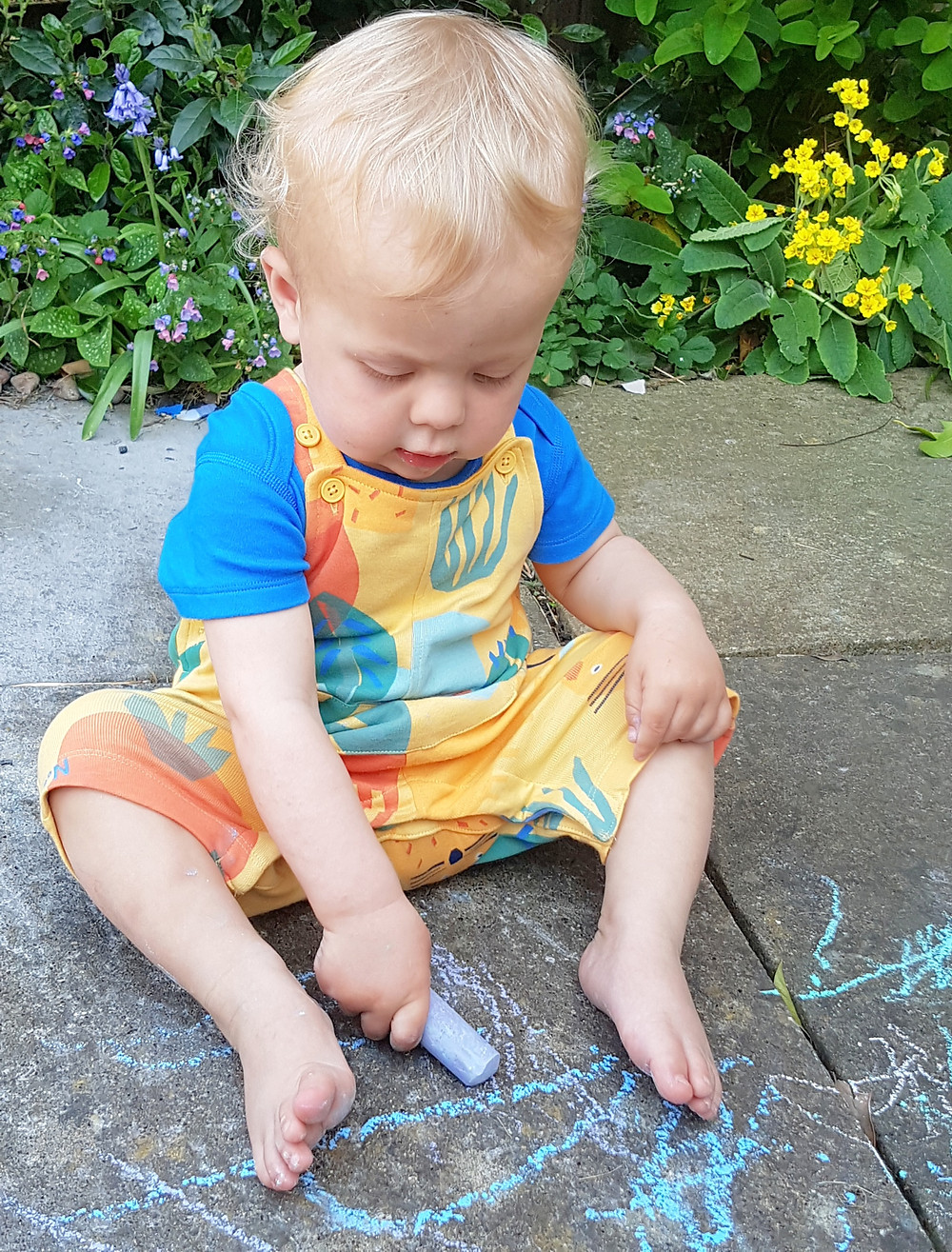 Baby drawing on patio with chalks