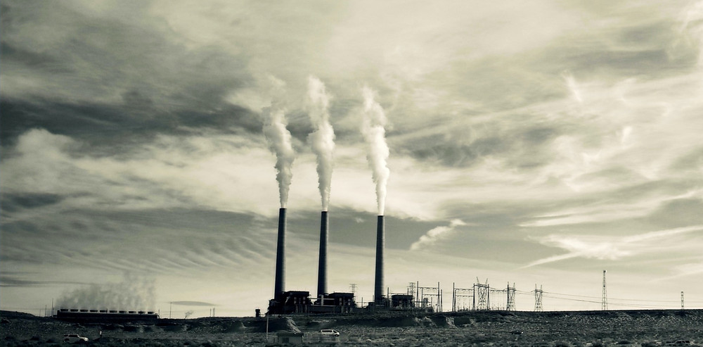 Image of three industrial chimneys releasing pollution in air