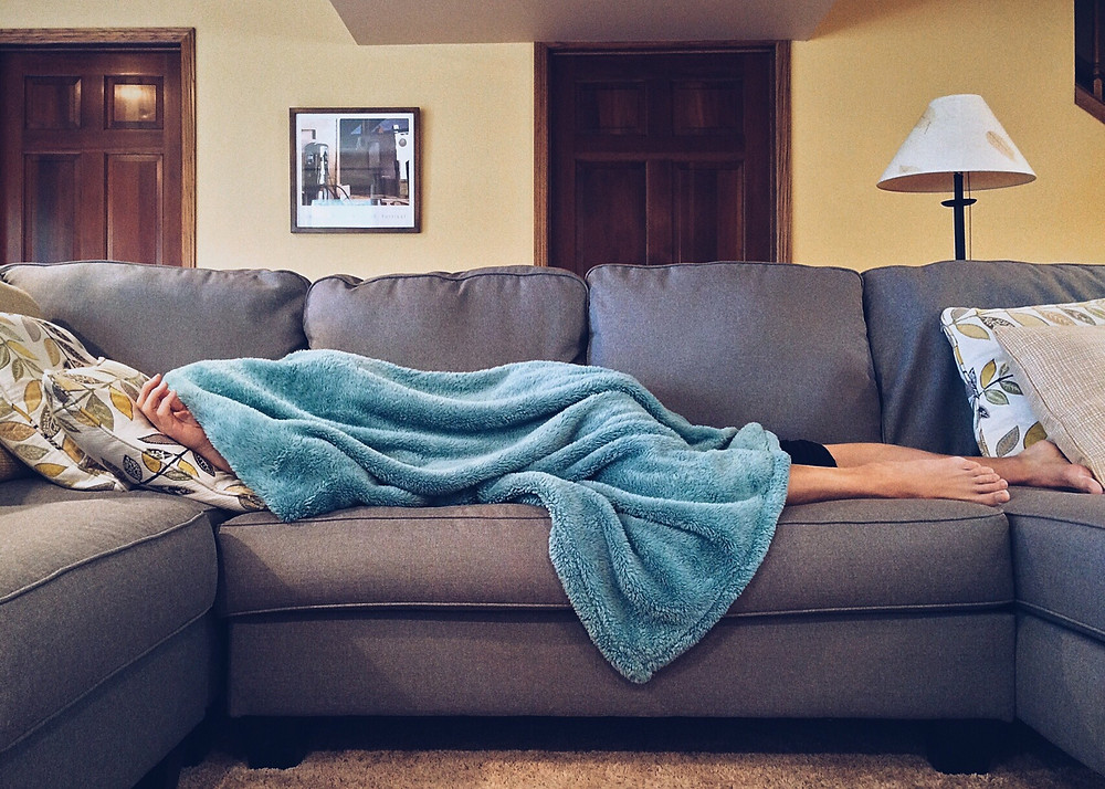 The flu forces person to take a sick day under a blue blanket on a couch.