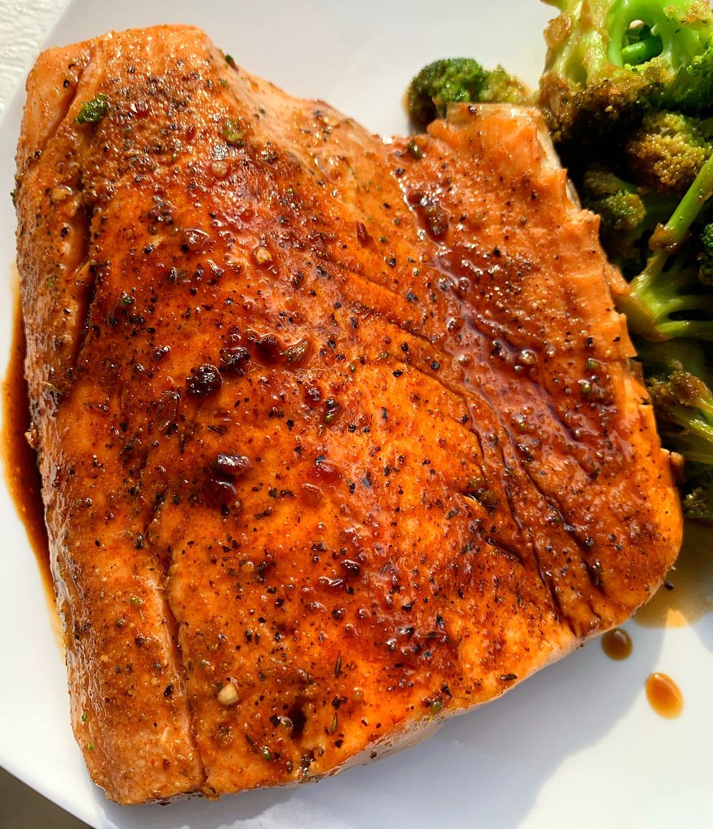 overhead shot of garlic honey soy glazed salmon, with seared broccoli in the background