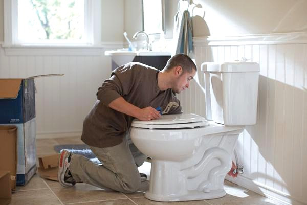 In the photo, someone is fixing a toilet. This photo is part of a blog for eConserve, a multifamily water conservation company.