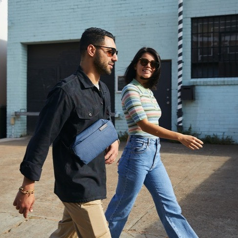 Two people walk side by side, one wearing a Bellroy sling.