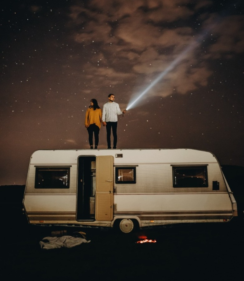 A couple stand on top of a caravan holding hands. It's dark and stars shine in the sky. One person shines a torch into the darkness.