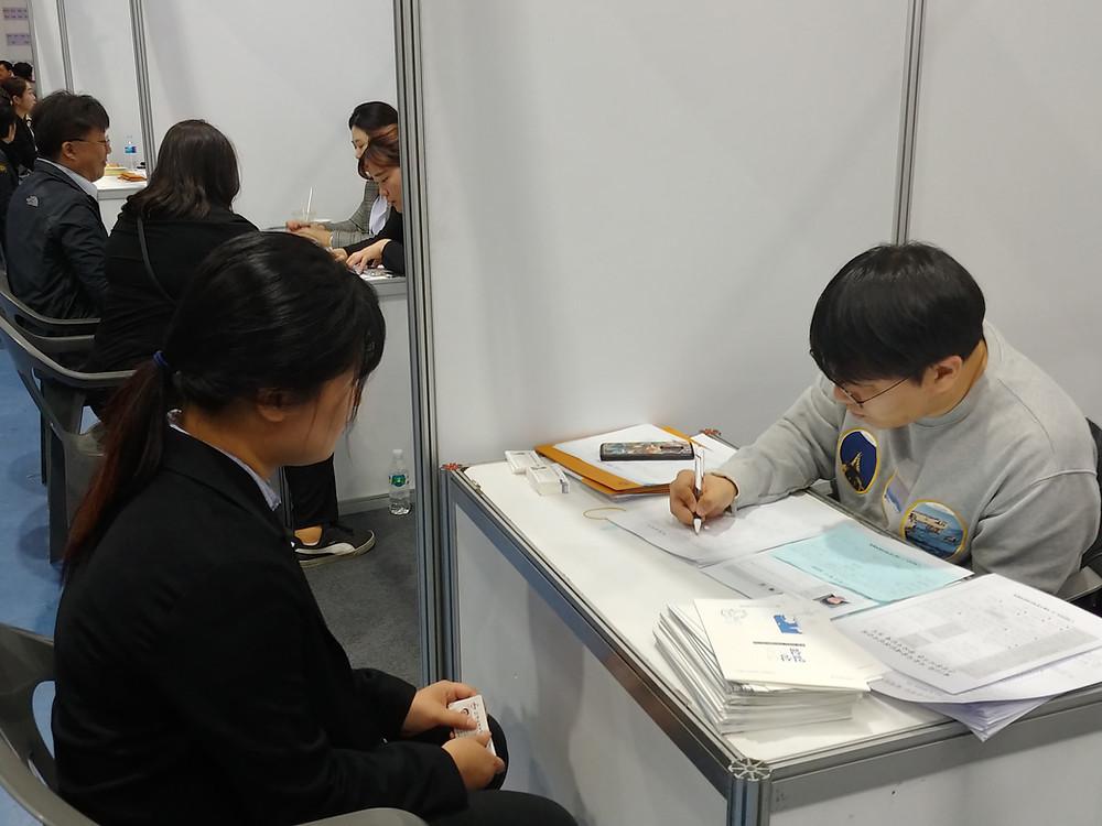 이력서와 구직신청서를 내고 면접을 보고 있는 참가자의 모습
