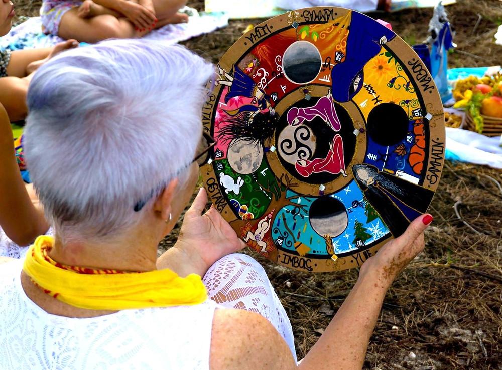 uma mulher segurando uma roda do ano da Deusa