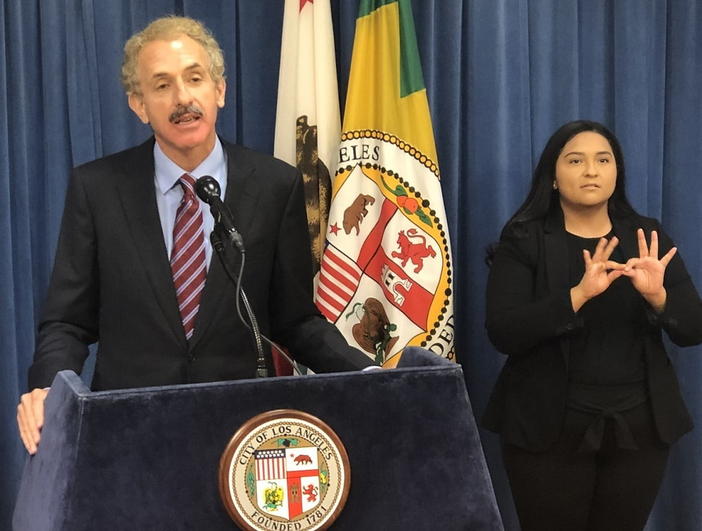City Attorney Mike Feuer in suit and tie at a podium with a microphone, wtih an American Sign Language interpreter behind him. both in front of a dark blue curtain.