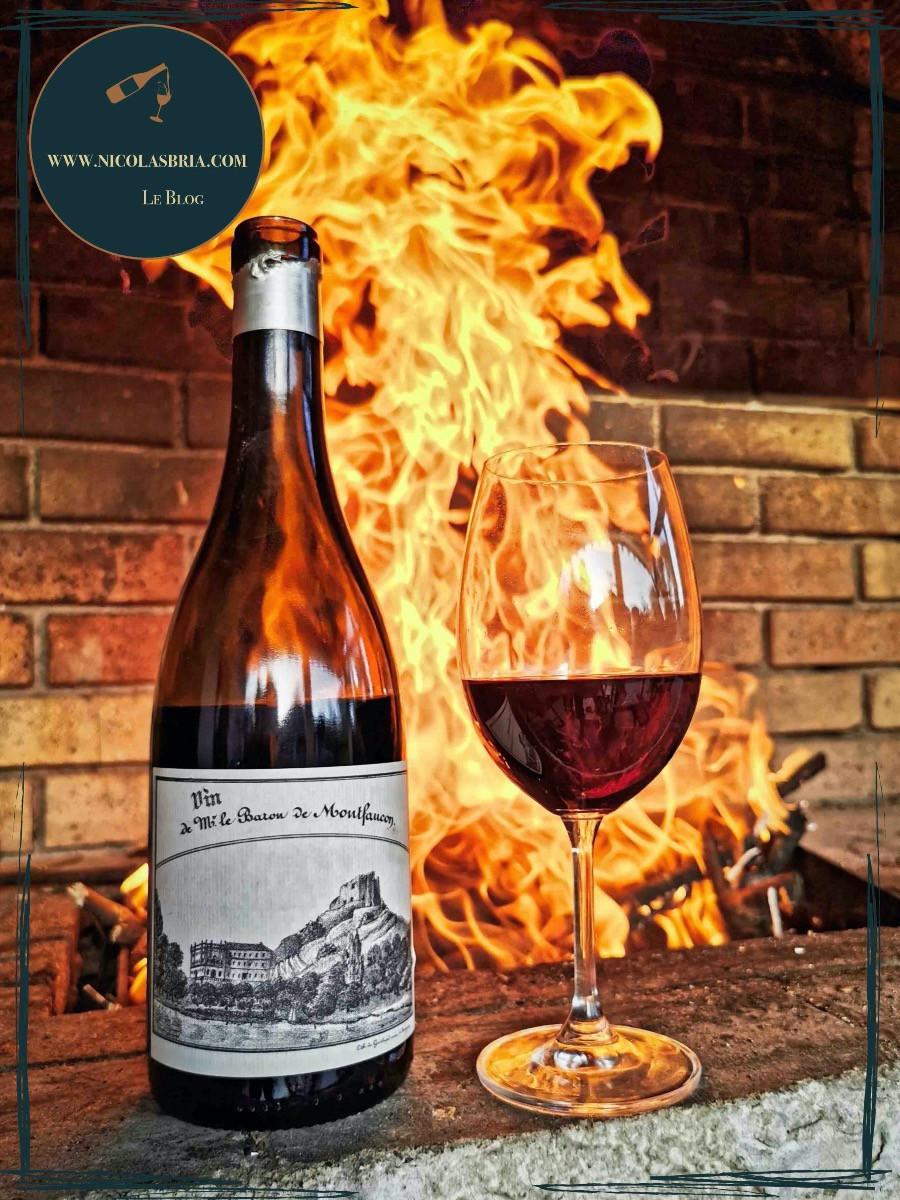 """On y voit la cuvée """"Vin de Monsieur le baron de Montfaucon, sur le bord d'un barbecue en briques. dans le fond, les flammes sont fortes et droites."""