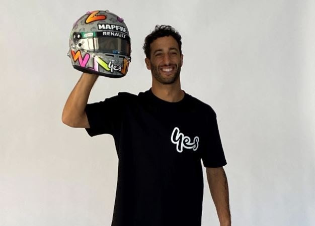 Optus brand ambassador Daniel Ricciardo posing with his helmet, which features the Oputs 'yes'