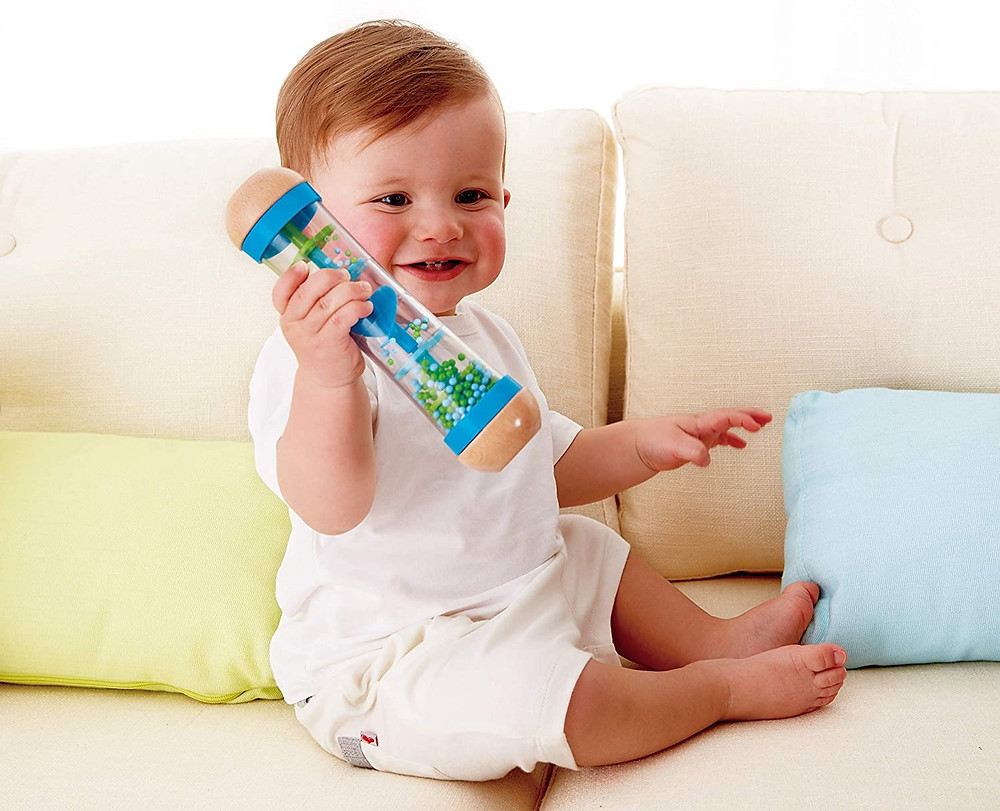 Smiling baby sitting up and holding rainmaker musical toy