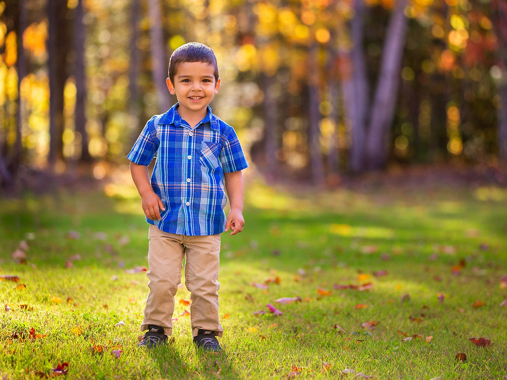 A boy posing for a portrait outside in the fall