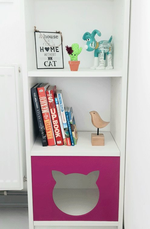 Tall, narrow Billy bookcase. Books an ornaments on shelves. Cat shaped panel fixed to the baottom shlef.