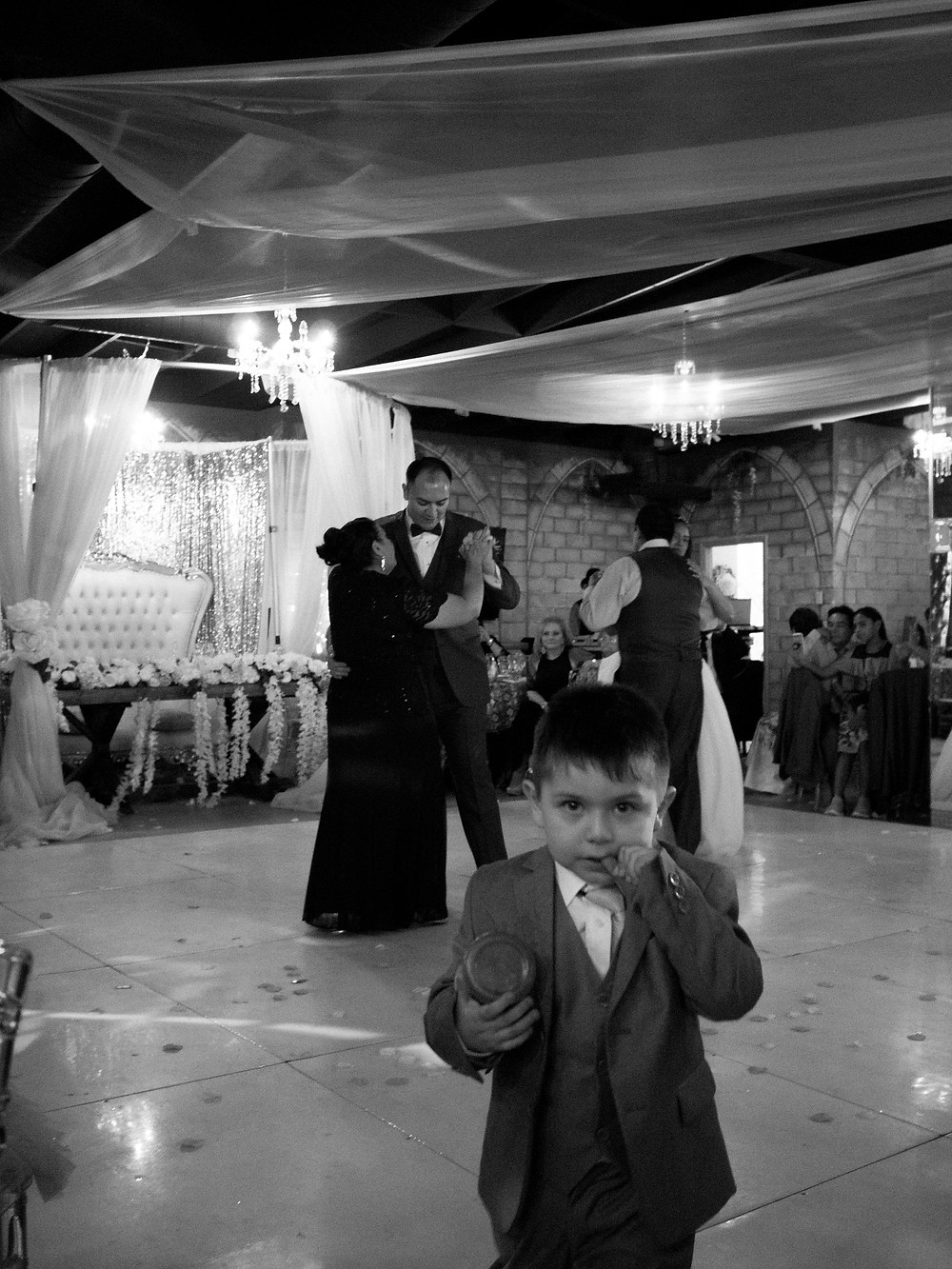 Handsome little gentleman looking at the camera with wedding couples dancing in the background