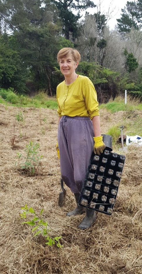 Volunteer (Coral) standing and smiling with some planting equipment