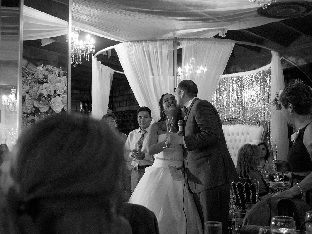 Groom kissing the bride on the cheek during speeches