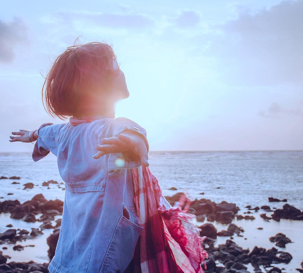 mulher de bracos abertos de frente para o mar