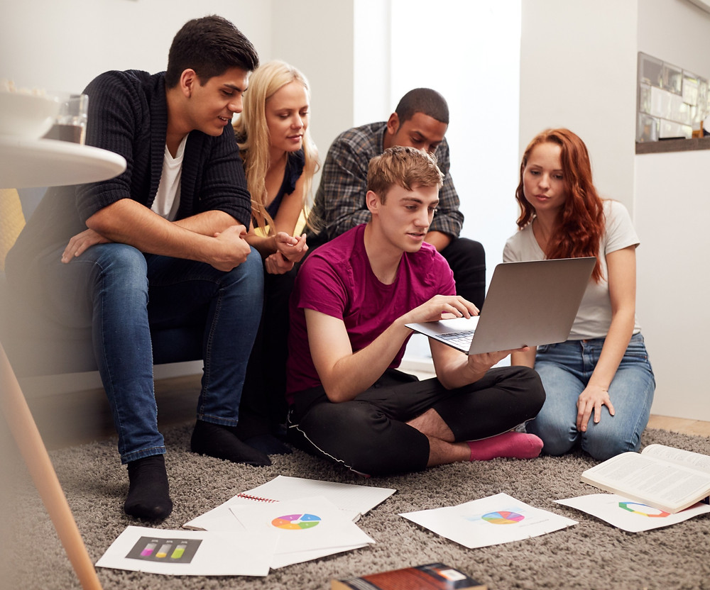 A group of school students revising for their secondary school exams, looking at laptop with revision paper on floor