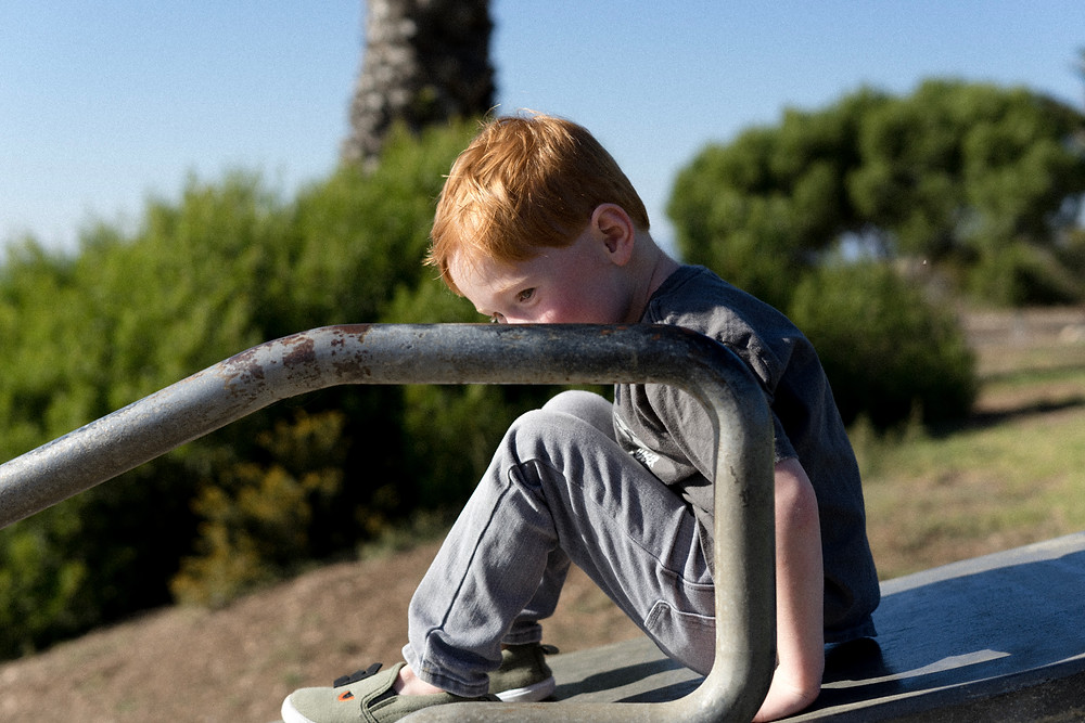 Young boy with red hair thinking about going down a slide