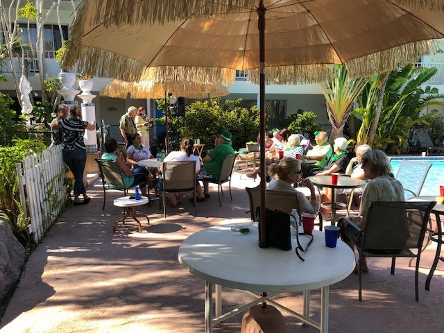 Guests listening to music sitting in chairs and under umbrellas at the front of the pool