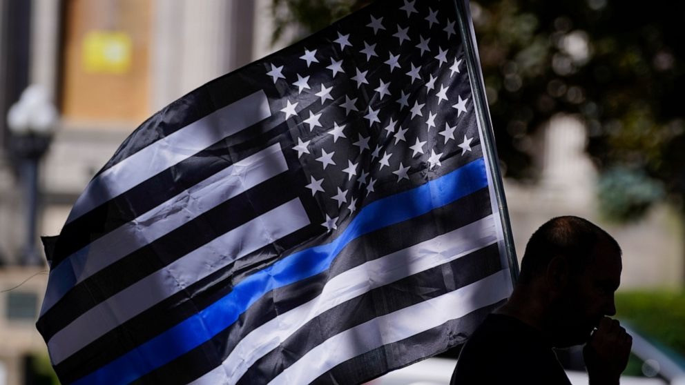 Man carrying Thin Blue Line flag.