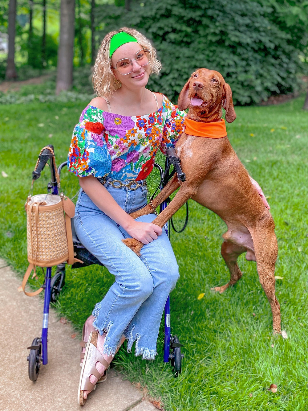 Cienna sits on her blue walker wearing a lime green cooling headband, tinted silver sunglasses, a rainbow floral puff sleeve top, gold chain belt, high waisted flared fringed blue jeans, and Birkenstock slide on sandals. Her service dog Piper has his paws on her and is wearing a bright orange cooling headband around his neck. They are both smiling at the camera.