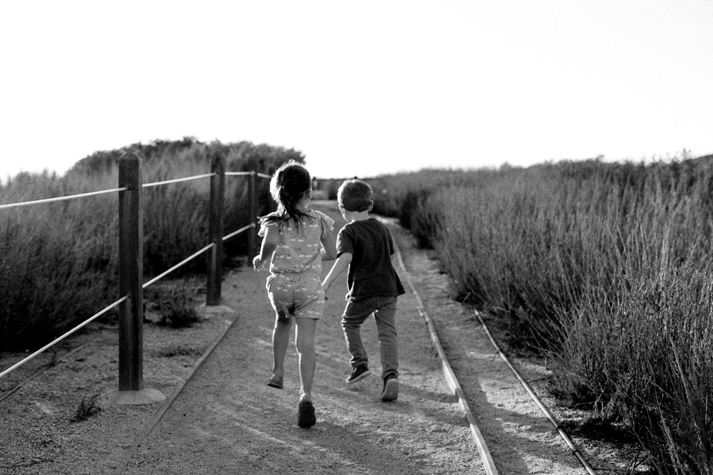 Young boy and girl running away from the camera