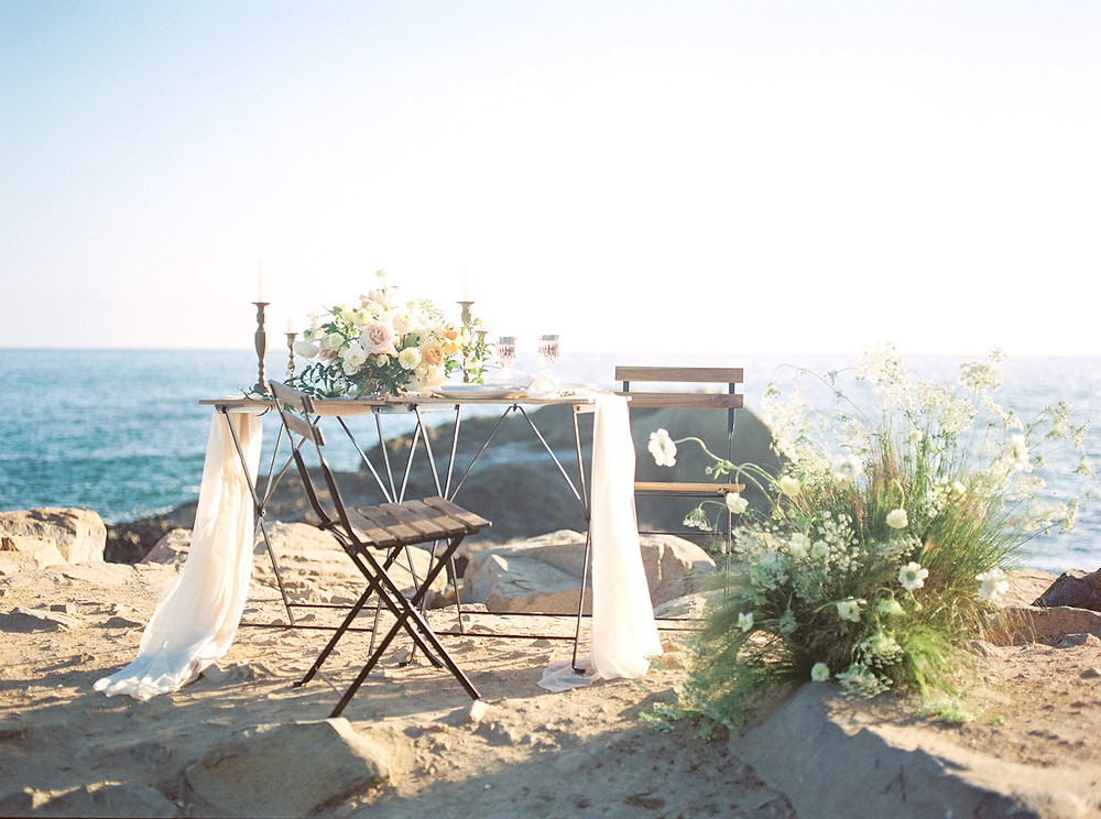 Gorgeous and intimate late Summer seaside Elopement setup/inspiration on the beach in Dana Point with beautiful golden and blush flowers on sweetheart table for two, paired with a growing foam free flower installation by San Diego Wedding Florist Le Champange Projects
