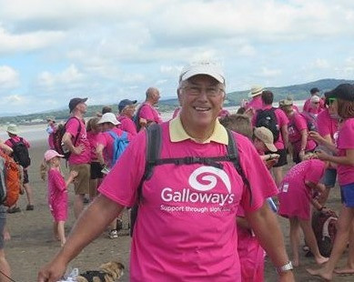 Peter is stood on the Morecambe Bay sands. He is wearing a pink Galloway's T-shirt and white cap. In the background are other Morecambe Bay Walk participants