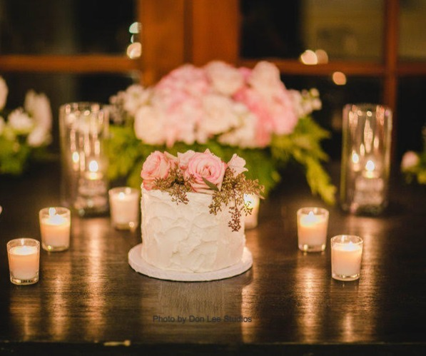 A Small Wedding Cake is sitting on the table before the bride and groom cut it during their wedding. The wedding planner decorated the farmhouse style table with candles and flowers at Calamigos Ranch in Malibu, CA.