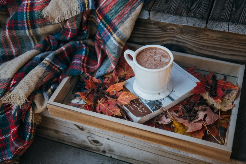 A cup pf hot chocolate in a box covered with autumn leaves, on top of a book , perfect for me-time