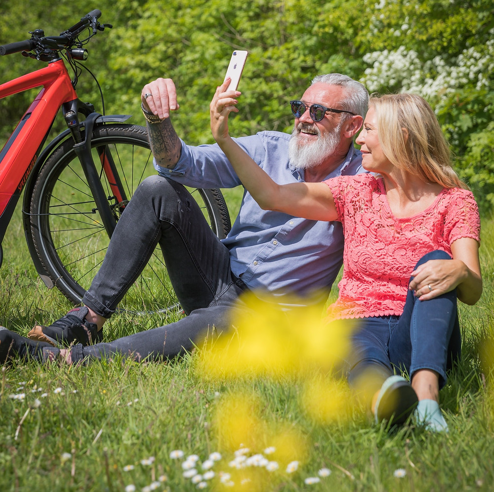 couple sitting in the grass by EBikes and taking a selfie.