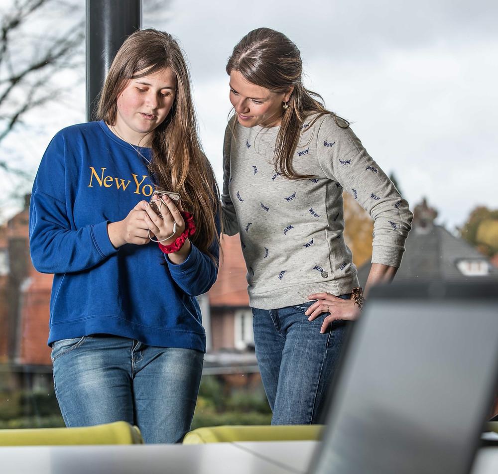 Een foto van een leerling en docent. Ze kijken samen naar de mobiele telefoon die de leerling in haar hand heeft.