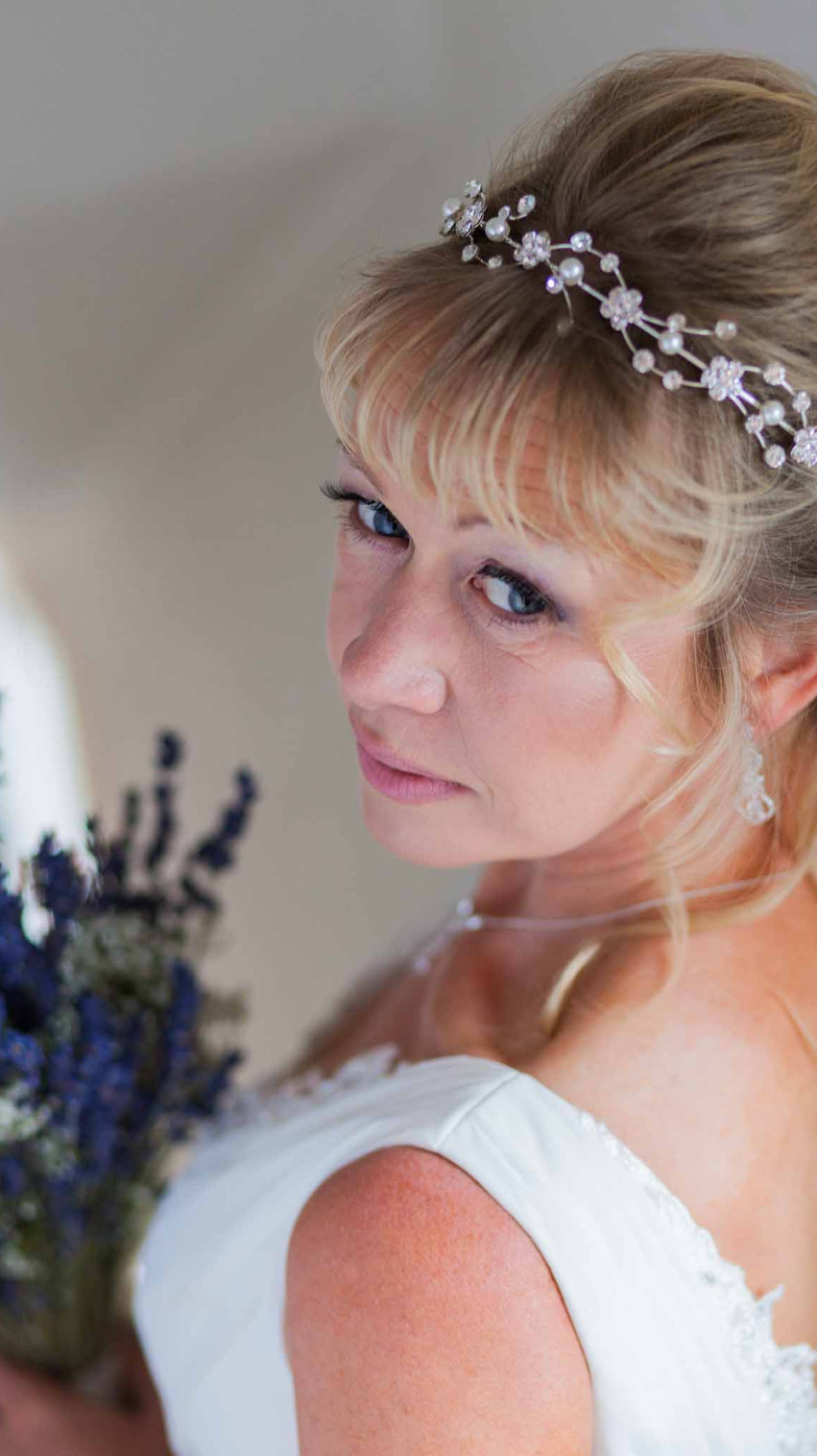 bride in a white wedding dress looking over her shoulder at the camera