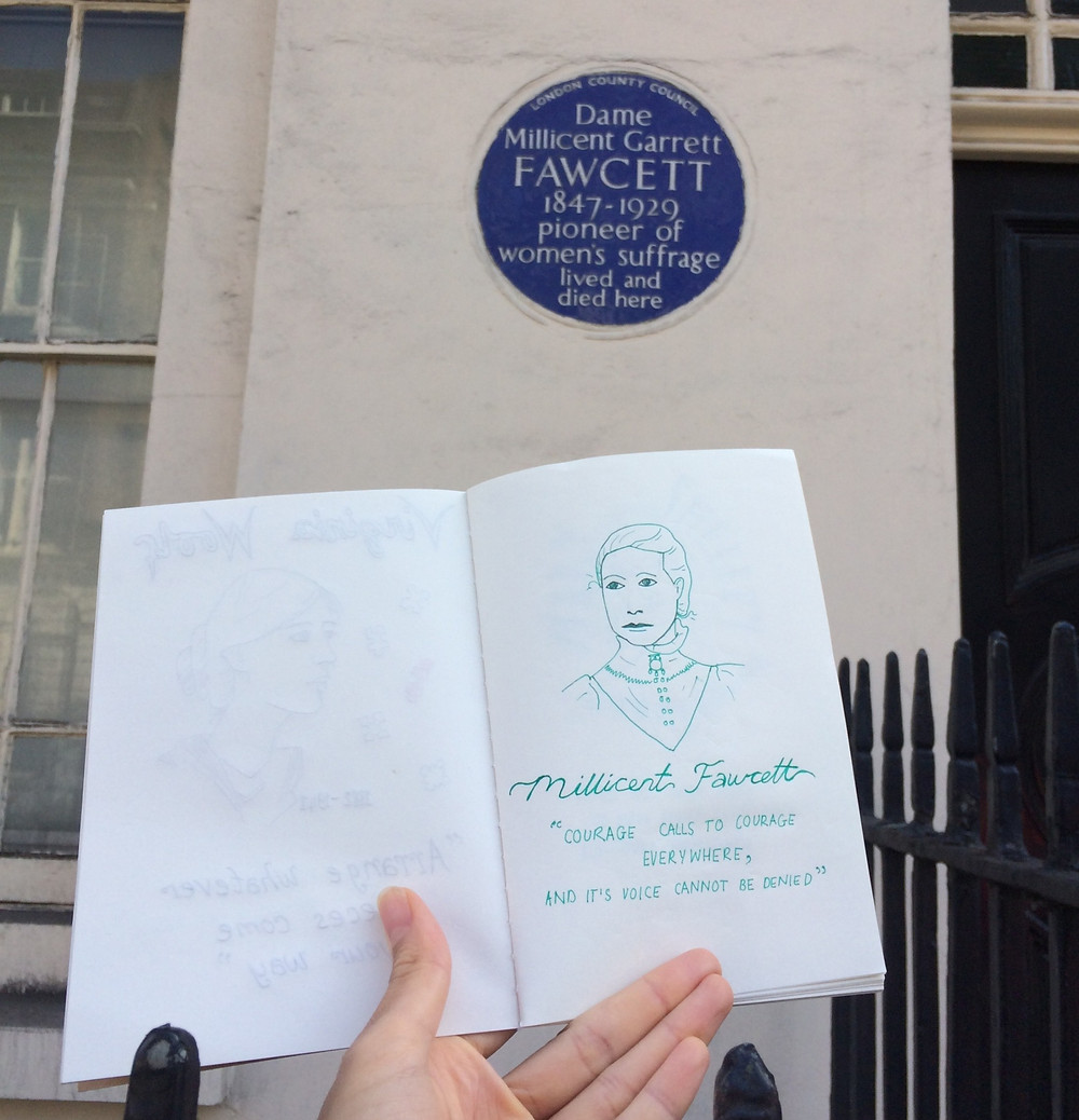 Nina holding up a sketch of Dame Millicent Garrett Fawett next to her blue plaque in London.