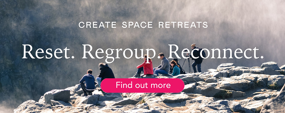 Group of people on a corporate retreat sitting on rocks
