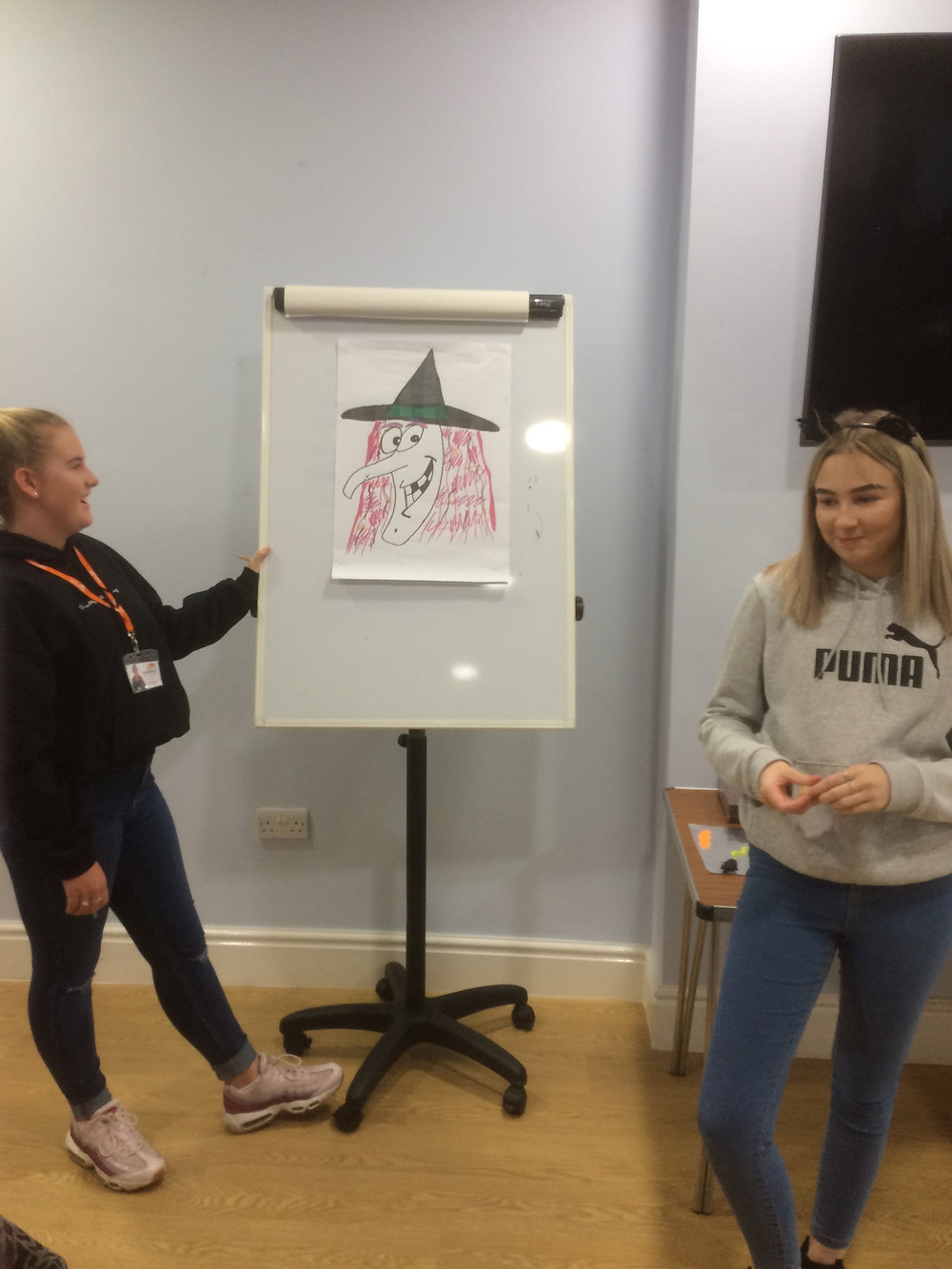 Olivia is stood holding a flip chart which has a drawing of a witch. Rebecca is stood at the other side