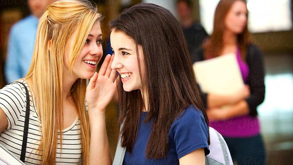 Dos jóvenes chismeando.