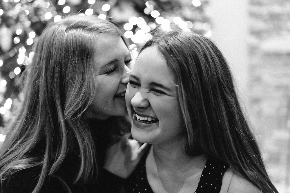 Sisters laughing in front of a Christmas tree