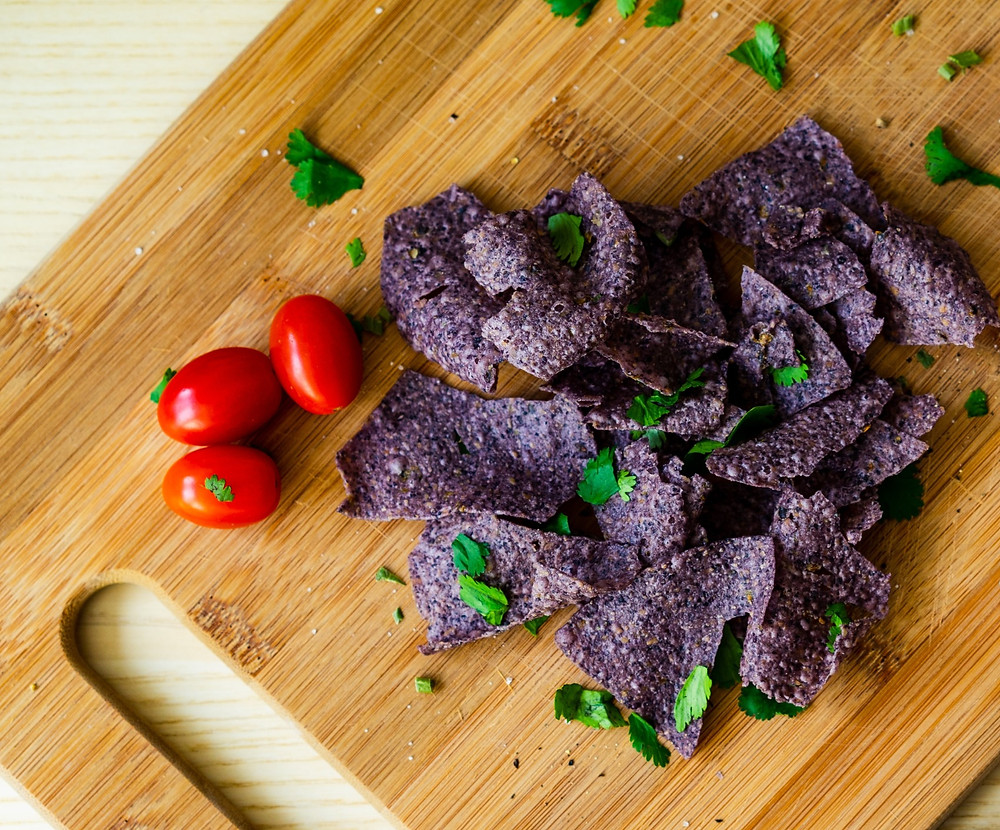 blue tortilla chips and cherry tomatoes on a cutting board