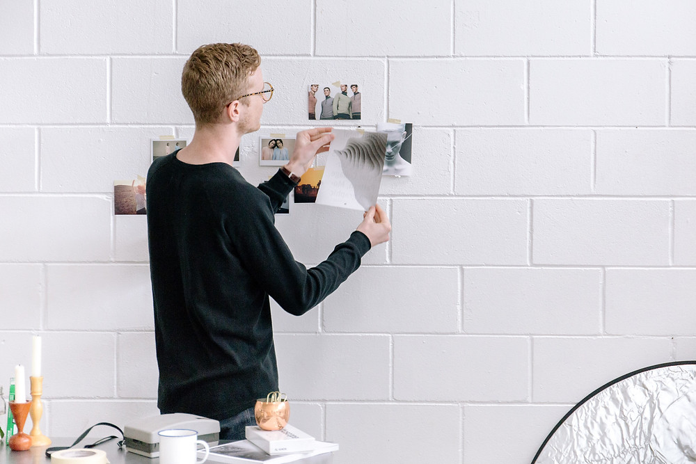 Creative strategist working in a digital ad agency putting printed inspirational photographs on the office meeting room wall