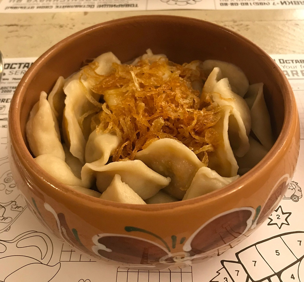 Bowl of various dumplings with onions on top, Moscow Russia