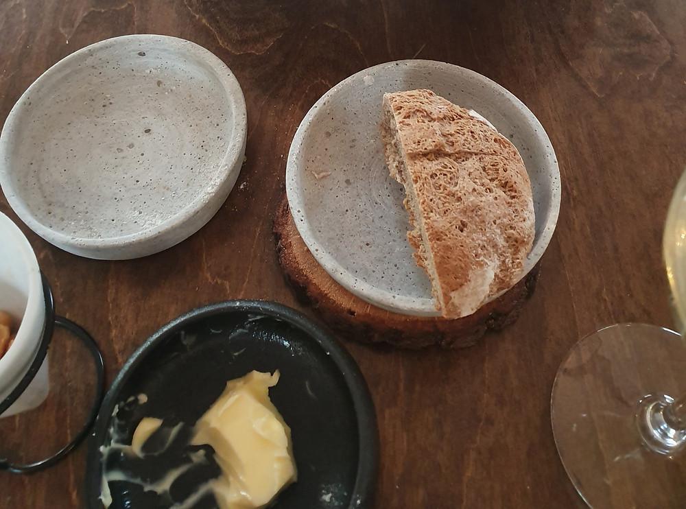 Eine Hälfte Brot, ein leerer Teller und ein Rest Butter in Keramiktellern