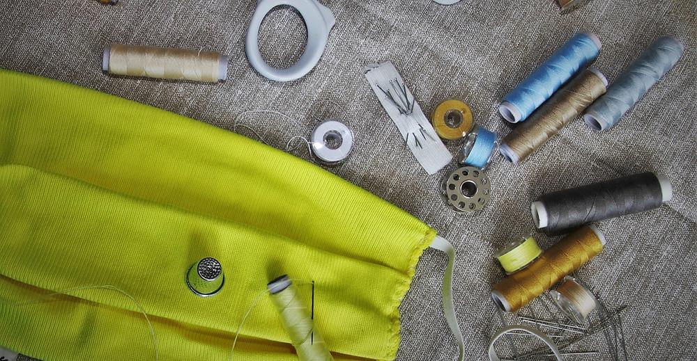 Sobre um tecido grosso estão: Uma máscara costurada a mão e instrumentos de costura como carretéis de linha, agulhas e um dedal. Na parte superior aparece um dos anéis de uma tesoura.