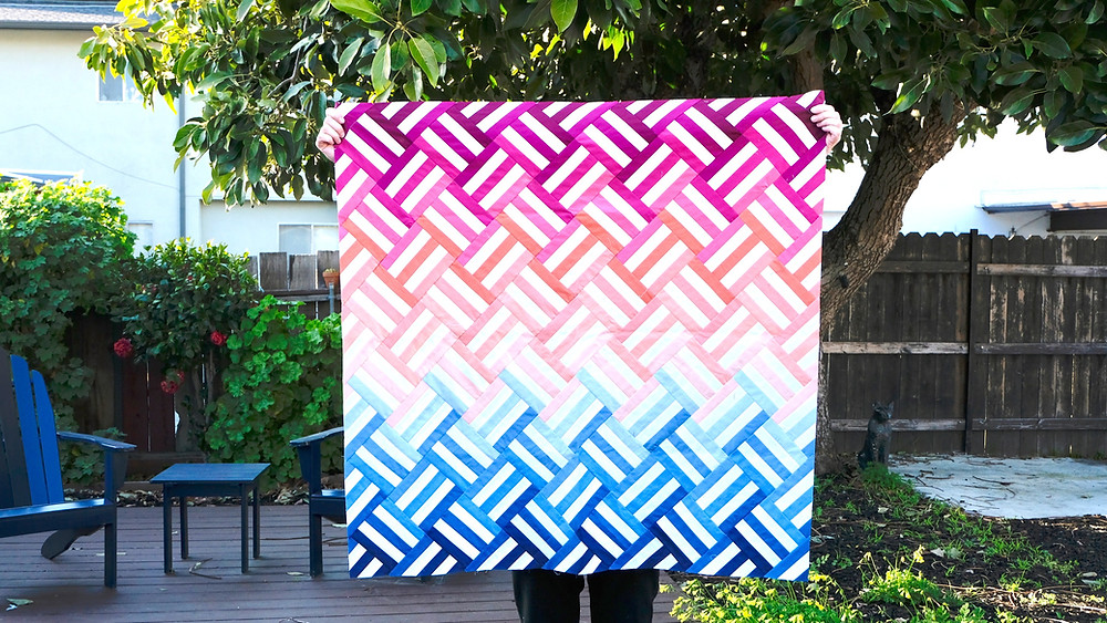 Purple orange pink blue weighted quilt in back yard