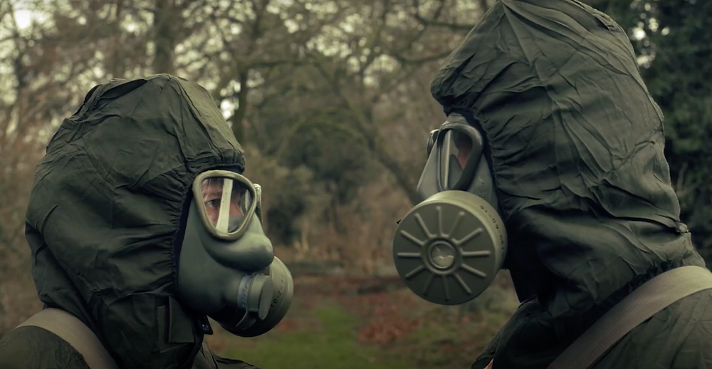 Still from 'Sync' featuring two characters facing one another wearing hazmat suits and gas masks