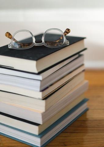 Kirjoja pinossa puisella pöydällä ja päällimmäisenä silmälasit