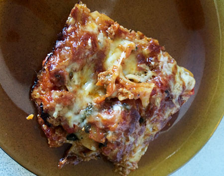 Left: A tray containing 12 slices of lasagna. Right: One slice of lasagna ready to eat on a plate.